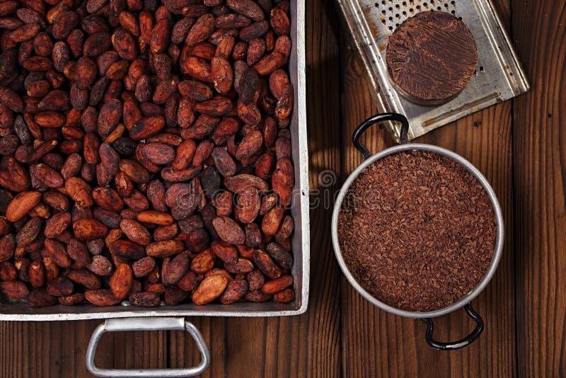 Zerriebene dunkle Schokolade im Zinn mit Kakaobohnen und festem Stück herein lizenzfreie stockfotos