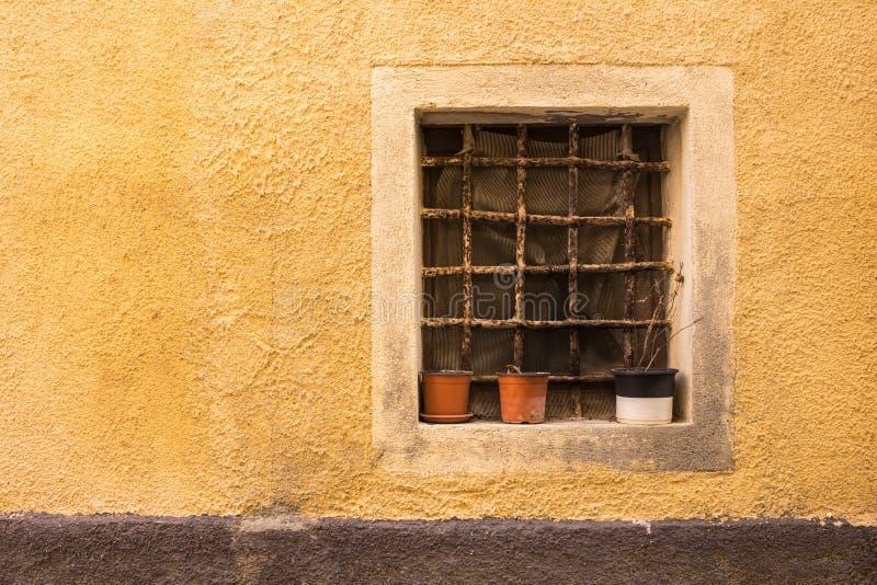 Zerriebenes Fenster mit leere Blumentöpfe Castelsardo, Sardinien, I lizenzfreies stockbild