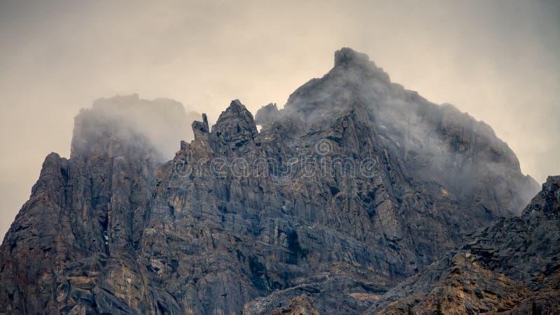Zerrissene Bergspitze umgeben durch stürmische Wolken stockfotografie
