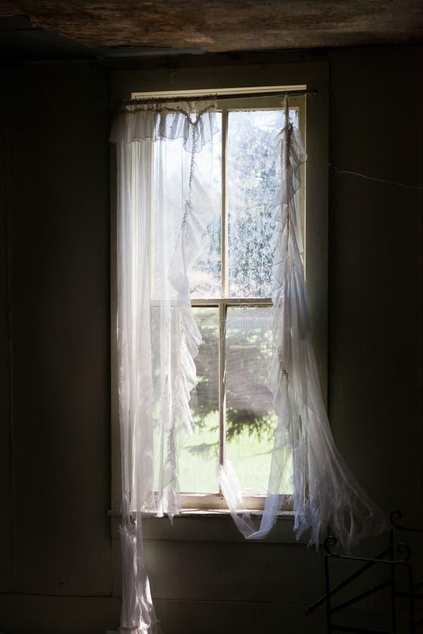 Zerrissener Vorhang auf verlassenem Gehöft-Fenster stockfotos