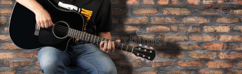 Zersplittern Sie Mann, eine schwarze Akustikgitarre auf einem alten Backsteinmauerhintergrund zu spielen stockbild