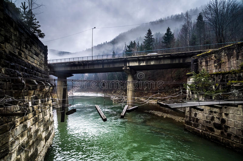 Zerstörte Fußgängerbrücke und Straße-brigde über dem Fluss in den Bergen lizenzfreies stockfoto