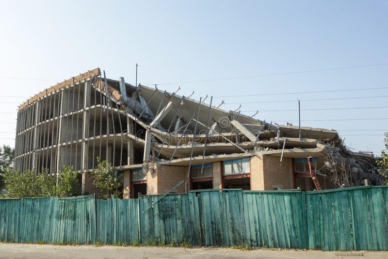 Zerstörtes Gebäude hinter einem grünen Zaun lizenzfreies stockfoto