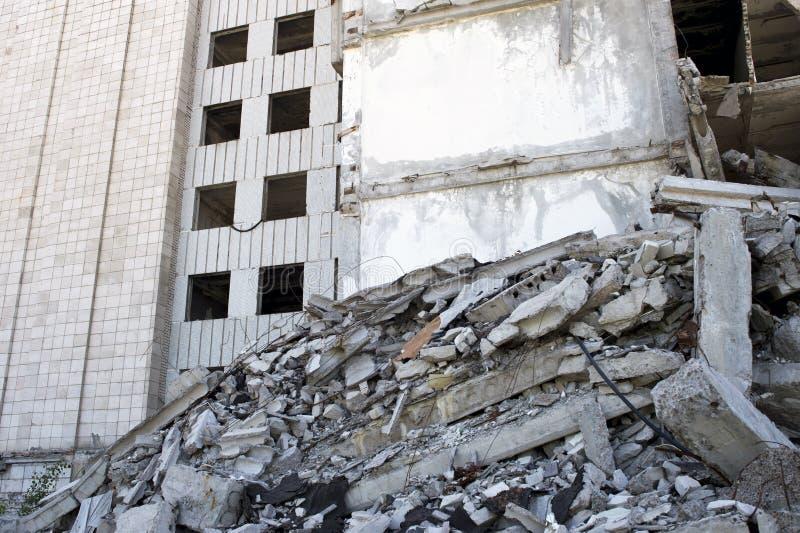 Zerstörtes großes Gebäude mit einer Blockierung des konkreten Rückstands im Vordergrund Hintergrund stockfotografie