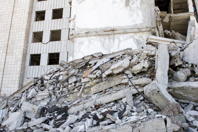 Zerstörtes großes Gebäude mit einer Blockierung des konkreten Rückstands im Vordergrund Hintergrund stockbild