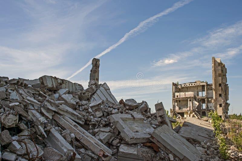 Zerstörtes großes Gebäude mit einer Blockierung des konkreten Rückstands im Vordergrund Hintergrund lizenzfreies stockbild