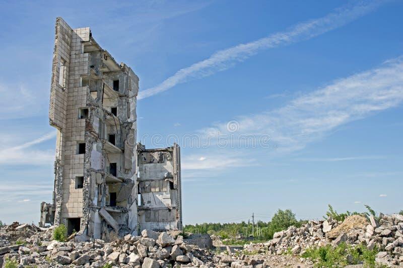 Zerstörtes großes Gebäude mit einer Blockierung des konkreten Rückstands im Vordergrund Hintergrund lizenzfreies stockfoto