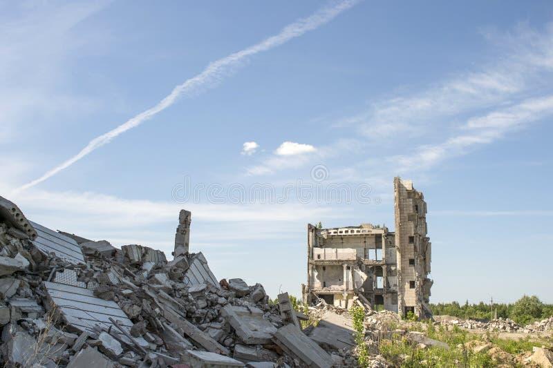 Zerstörtes großes Gebäude mit einer Blockierung des konkreten Rückstands im Vordergrund Hintergrund stockfotos