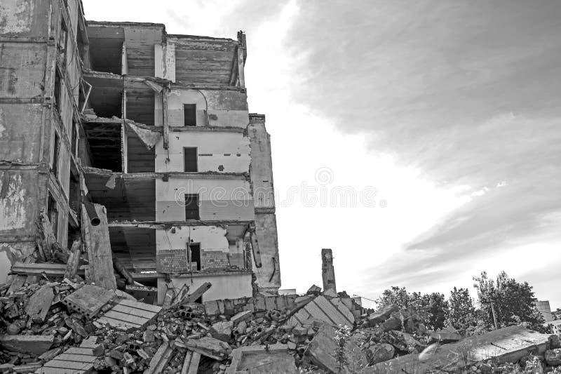 Zerstörtes großes Gebäude mit einer Blockierung des konkreten Rückstands im Vordergrund Hintergrund stockfoto