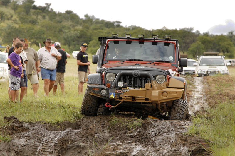 Zerstampfungs-beige Jeep Rubicon-Überfahrtschlammhindernis lizenzfreies stockfoto