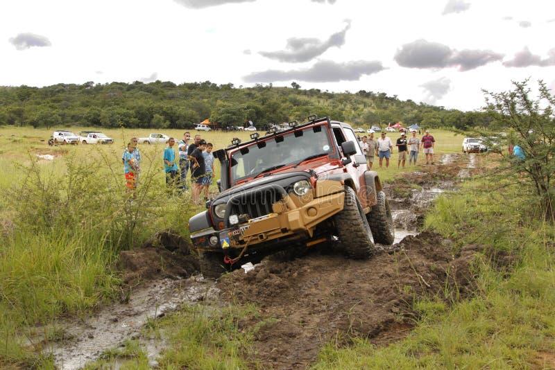Zerstampfungs-beige Jeep Rubicon-Überfahrtschlammhindernis lizenzfreie stockfotografie