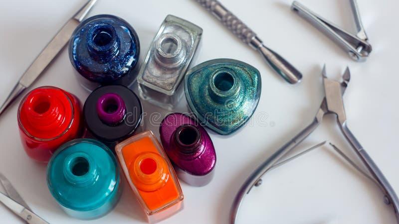 Zerstreuter Nagellack mit Maniküre- und Pedikürewerkzeugen im Schönheitssalon oder -Kosmetiksalon Die Wahl des Farbnagellacks für lizenzfreie stockfotos