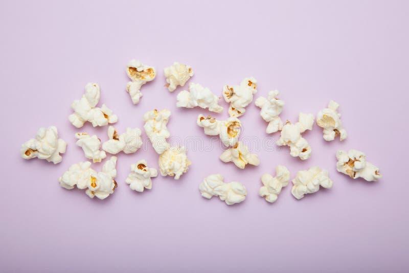Zerstreutes Popcorn auf einem rosa Hintergrund lizenzfreie stockfotografie