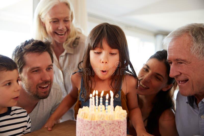Zes éénjarigen wit meisje die haar verjaardag met familie vieren die uit de kaarsen op haar cake blazen stock foto's