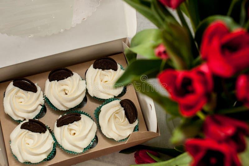 Zes cupcakes met witte die kaasroom met koekjes in een doos en een vaag boeket van tulpen hoogste mening wordt verfraaid royalty-vrije stock foto