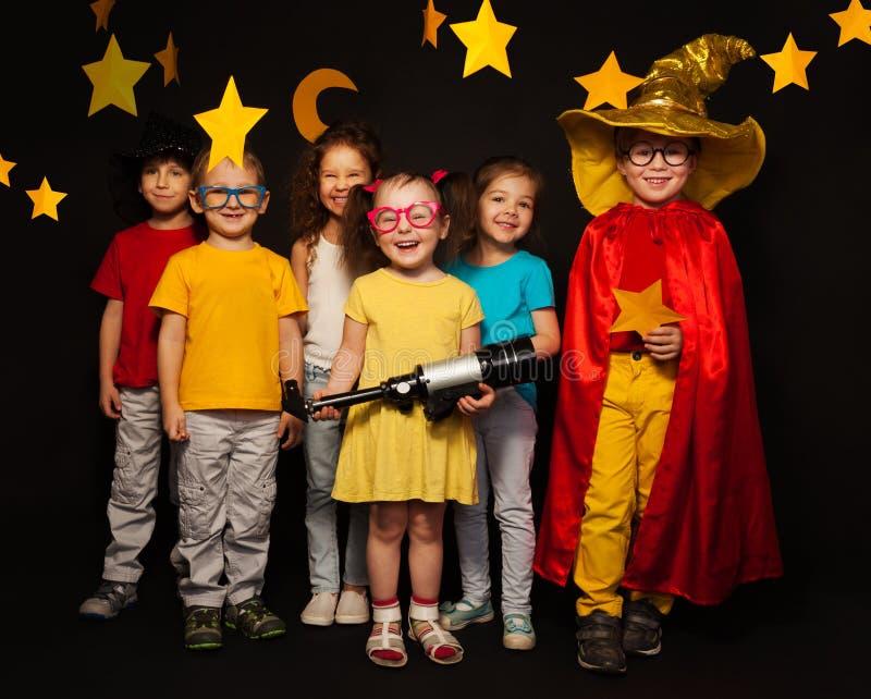 Zes jonge geitjes in dromerskostuums met telescoop royalty-vrije stock afbeeldingen