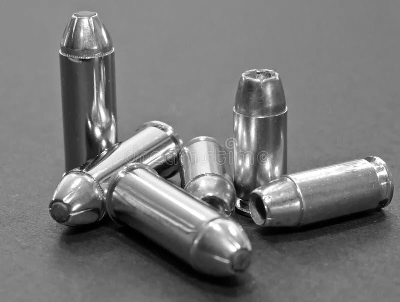 Zes kogels, drie 40 kaliber hol punt en drie 44spl op een grijze achtergrond royalty-vrije stock foto's