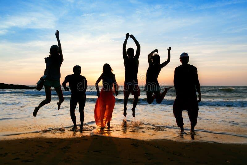 Zes mensen die op strand bij zonsondergang springen stock fotografie