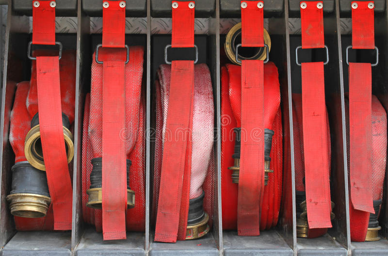 Zes rode slangen van brandbestrijders in orde binnen de brandvrachtwagen stock foto