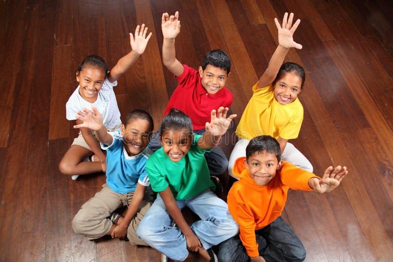 Zes schoolkinderen die in klaslokaalhanden omhoog zitten stock afbeeldingen