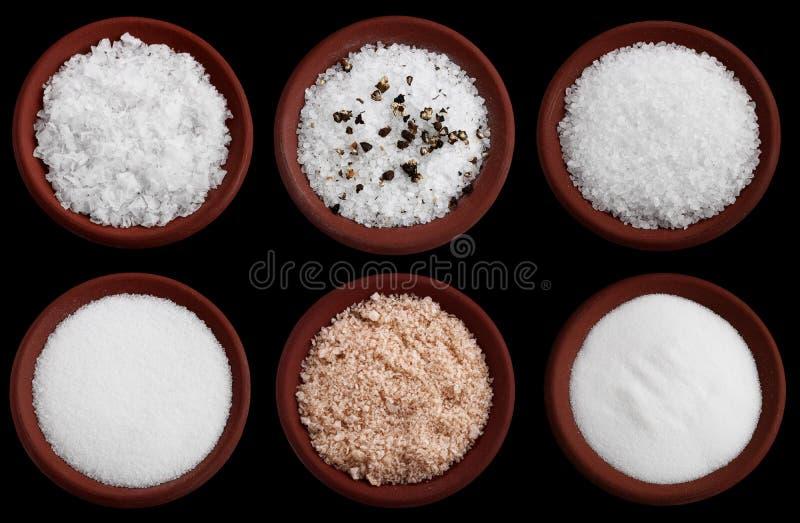 Zes terracottaplaten met overzees zout op zwarte stock foto