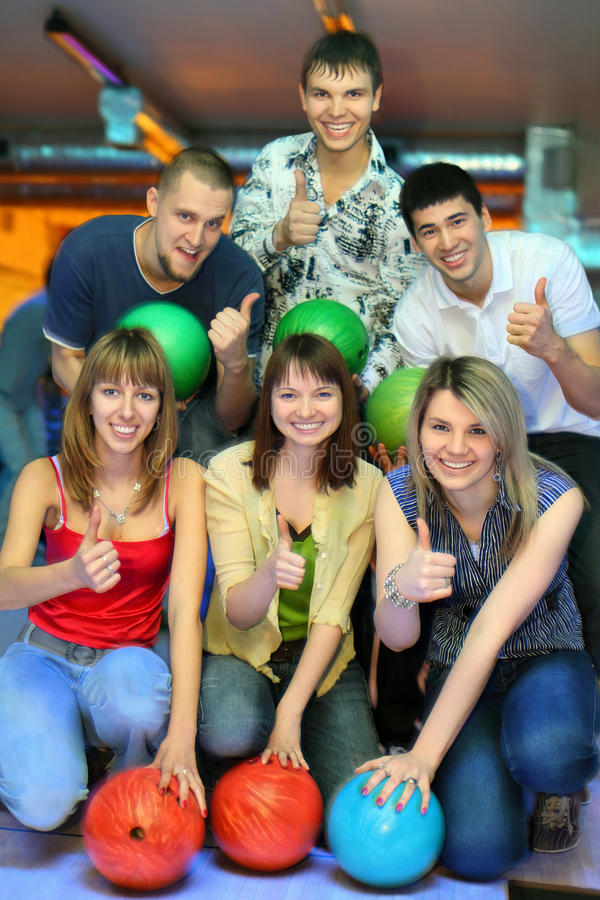 Zes vrienden met ballen voor kegelen tonen o.k. royalty-vrije stock foto's