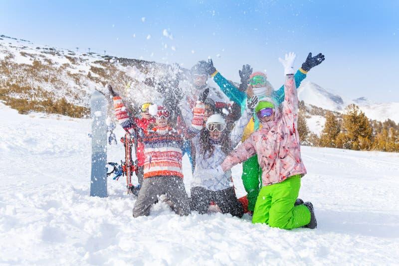 Zes vrienden met snowboards en skis die sneeuw werpen royalty-vrije stock foto