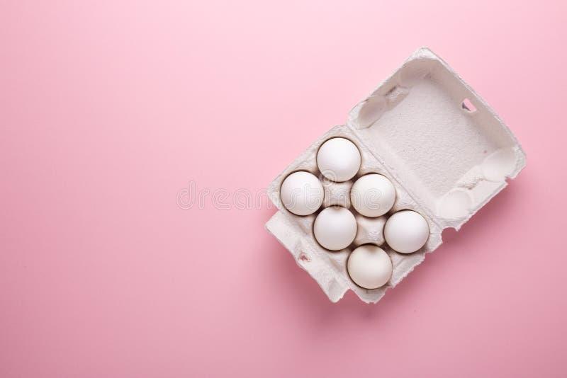 Zes witte eieren in kartonvakje op de roze document Vlakte van Pasen van het achtergrond Hoogste meningssymbool Gelukkige lagen stock afbeeldingen