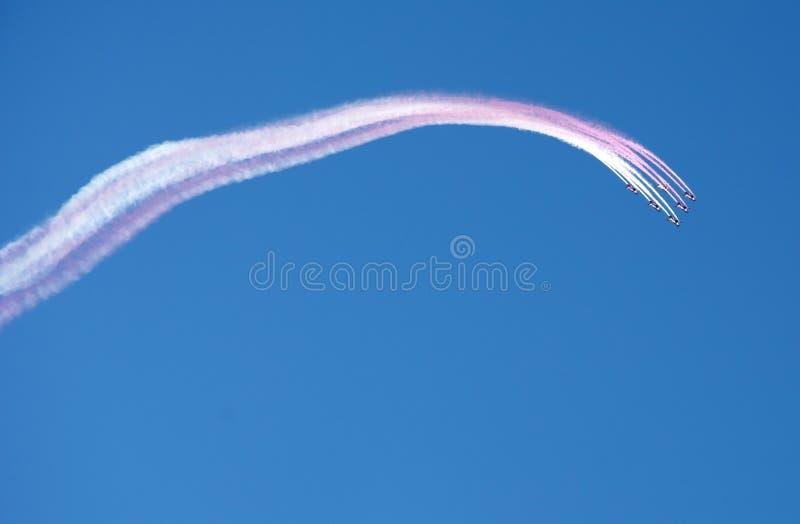 Zespół akrobatyczny lecący w formacji i zostawiający ślad białego różowego dymu na niebieskim niebie fotografia stock