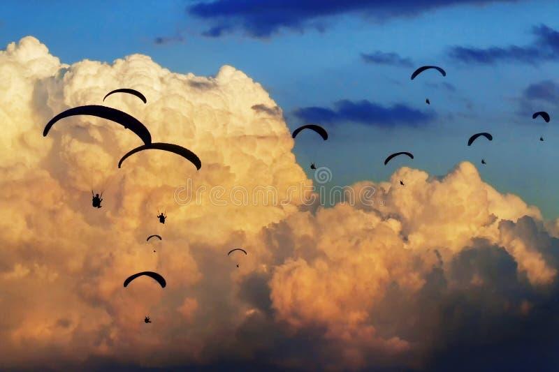 Zespół paragliders lata z gigantycznymi chmurami na tle zdjęcia stock