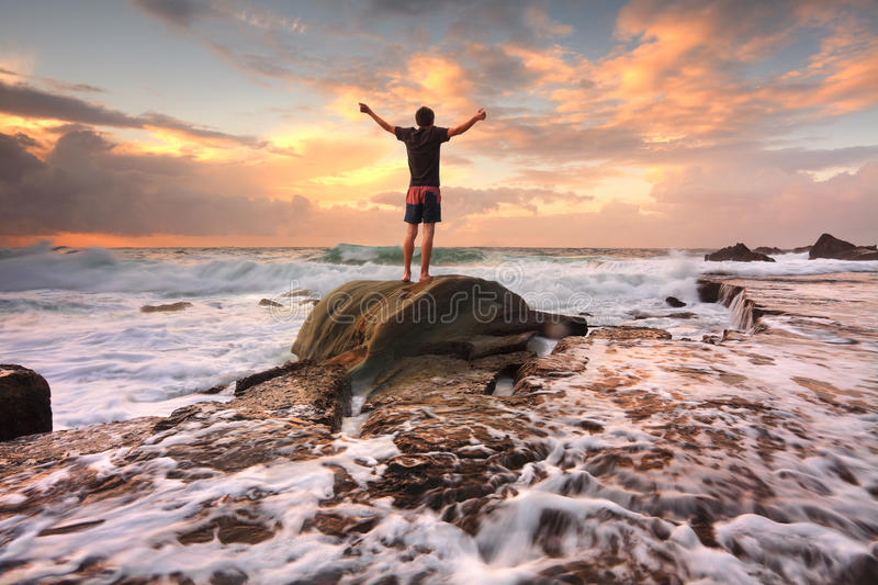 Zest Life, Praise God, Love Nature, Sunrise turbulent seas arms. Teen boy stands on a rock among turbulent ocean seas and fast flowing water at sunrise. Worship royalty free stock photography