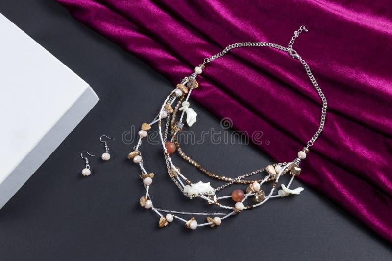 Zestaw kolczyków i wielowarstwowy kryształowy naszyjnik z kamieniami i skorupą morską srebrny łańcuch boho styl na czerwonym saty zdjęcia stock