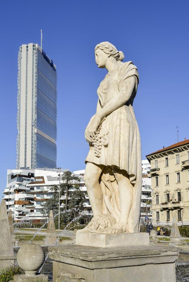 Zestawienie statua przy fontanną Cztery sezonu w piazza Giulio Cesare, Citylife, z Il Dritto drapaczem chmur w tle obraz stock