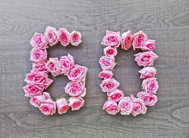 60, zestig - uitstekend aantal roze rozen op de achtergrond van donkere wood5 royalty-vrije stock afbeeldingen