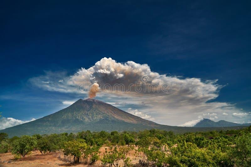 Zet Agung-vulkaan dramatische uitbarsting over donkerblauwe hemel op stock afbeelding
