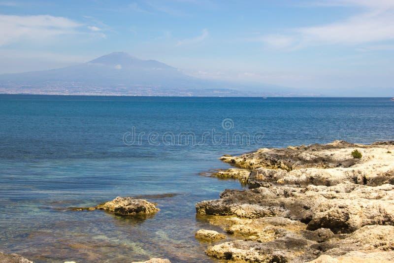 Zet de Brucoli toneelmening van rotsachtige kust, blauwe overzees en ver Etna op stock foto