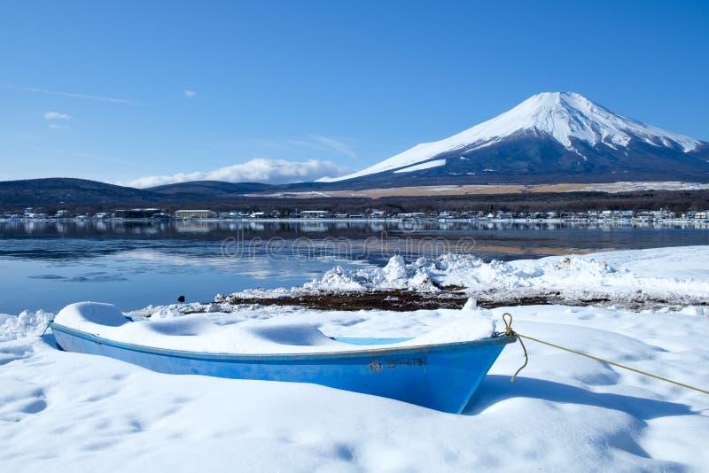 Zet Fuji met boot bij Bevroren Yamanaka-Meer in de Winter op stock afbeelding