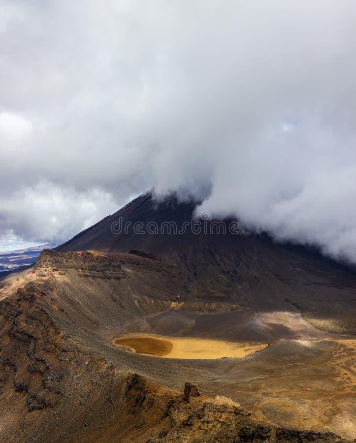 Zet Ngauruhoe op achter wolken in het Nationale Park van Tongariro, Nieuw Zeeland wordt behandeld dat stock afbeelding