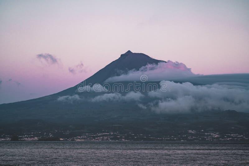 Zet Pico-vulkaan westelijke die helling op van oceaan tijdens volle maan met top in wolken na zonsondergang met roze hemel wordt  stock foto