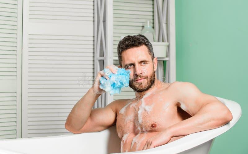 Zet uw badkamers in eigen priv? kuuroord om De macho met spons neemt thuis bad Het nemen van bad met zeepzeepsop pampering royalty-vrije stock foto's