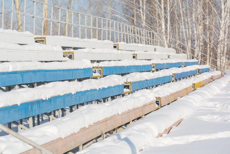 Zetels in het stadion onder de sneeuw Stoelen voor toeschouwers bij het stadion onder de sneeuw stock fotografie