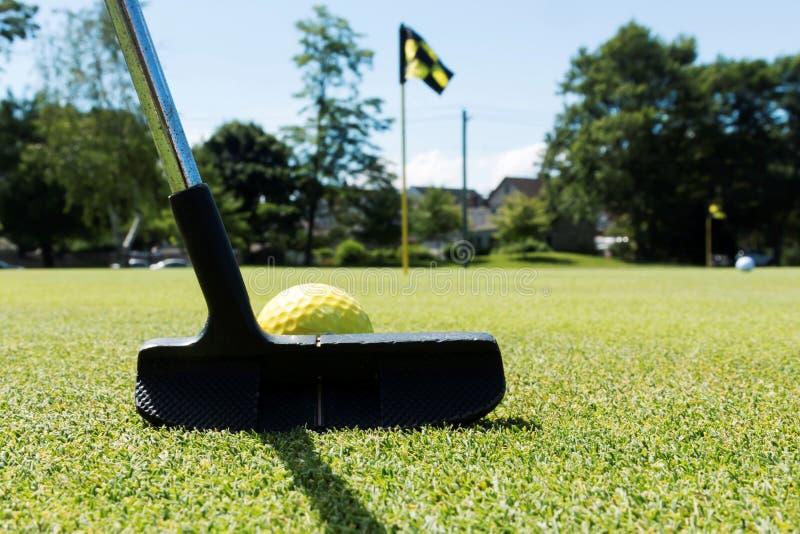 Zettend een gele bal op een groene praktijk royalty-vrije stock foto