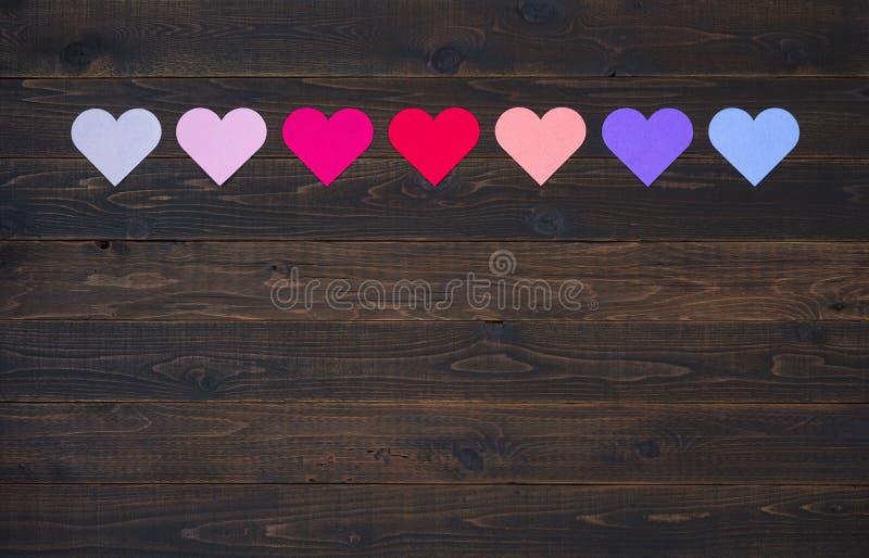 Zeven Harten in Diverse kleuren op rustieke houten raadsachtergrond royalty-vrije stock afbeelding
