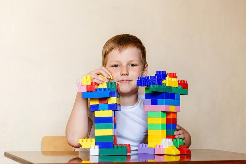 Zeven-jaar-oud kind in een witte t-shirt en de ontwerper van plastic kinderen royalty-vrije stock afbeeldingen