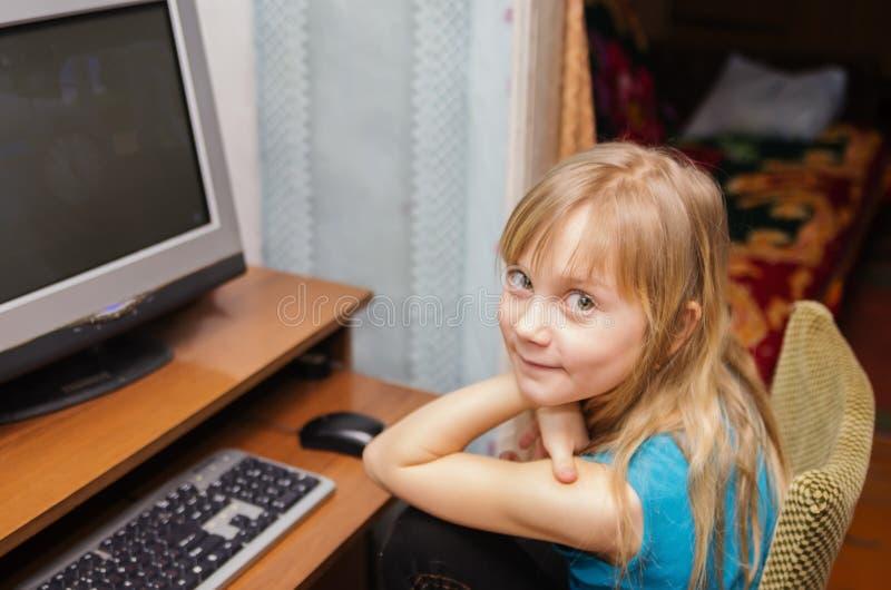 Zeven-jaar-oud meisje bij de computer stock fotografie