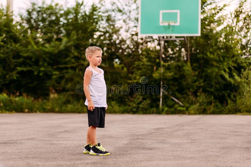 Zeven-jaar-oude jongen in basketbal eenvormige treinen op een open basketbalhof in de zomer Jonge geitjes en sporten, jongen in b royalty-vrije stock afbeelding