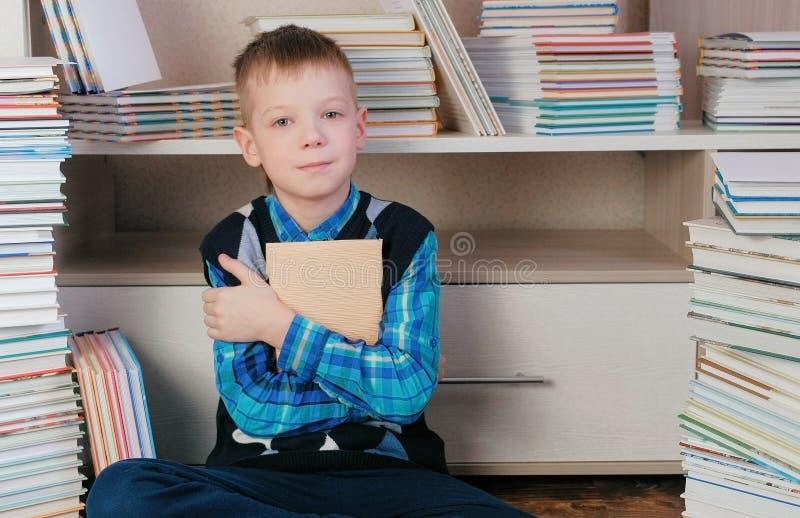 Zeven-jaar-oude jongen die het boek koesteren en bij de camerazitting glimlachen onder boeken stock foto
