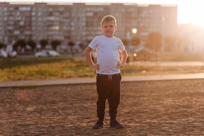 Zeven-jaar-oude jongen in een witte t-shirt in de volledige groei die de camera in het zonsonderganglicht bekijken in de stad royalty-vrije stock foto