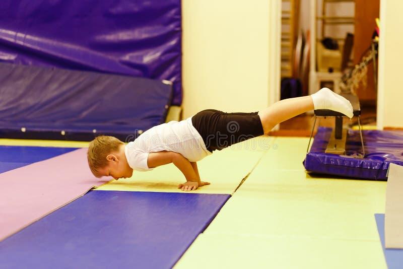 Zeven-jaar-oude jongen in eenvormige het doen handstand Kinderen` s yoga Oefeningskrokodil Acrobatische oefening stock afbeelding