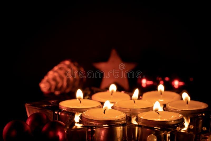 Zeven kaarsen die in een glascontainer branden stock foto